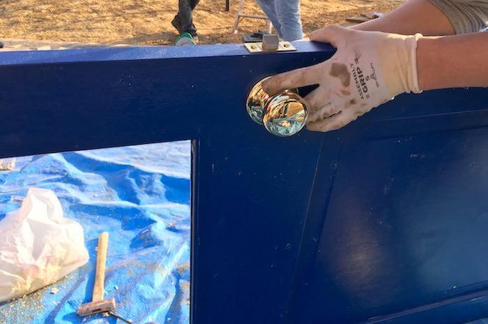 無垢材の扉にドアノブの取り付けとエイジング塗装を施し小屋に取り付ける